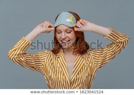 Stock photo: Time to sleep or go to bed. Glad ginger woman keeps gaze down, wears sleepmask and sleepwear, has ha