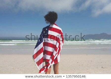 Rear view of beautiful Mixed-race woman wrapped in american flag while looking at the sea at beach o Stock photo © wavebreak_media