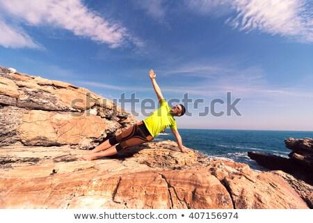 Young sporty fit man doing yoga meditating on tropical beach Stock photo © dmitry_rukhlenko