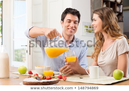 Young couple drinking orange juice together Stock photo © stockyimages