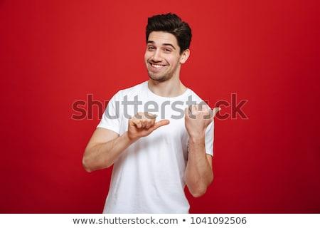 Fiatalember mutat portré mosolyog pont stúdiófelvétel Stock fotó © ajn