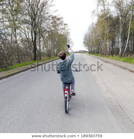 boy shoots a picture while riding bike Stock photo © meinzahn