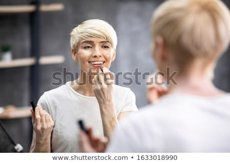 Beautiful middle aged woman applying lipstick stock photo © svetography