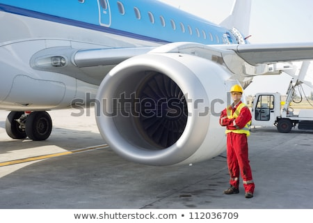 Repair man in overall fixing engine on a plane Stock photo © deandrobot