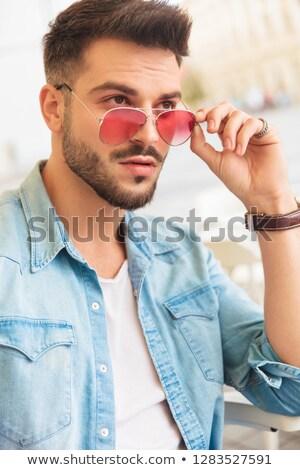 сидящий человека Солнцезащитные очки глядя сторона Сток-фото © feedough
