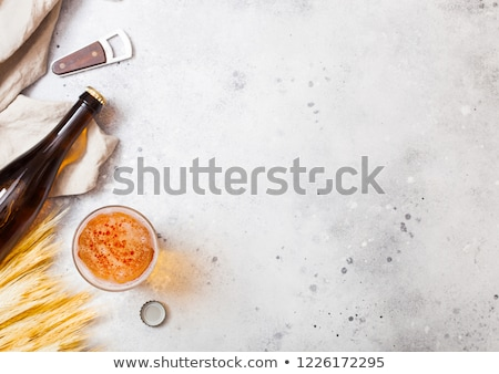 Glass and bottle of craft lager beer with raw wheat and opener o Stock photo © DenisMArt