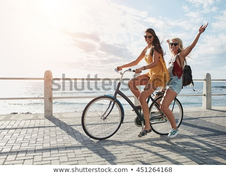Two young beautiful women friends outdoors with bicycles stock photo © deandrobot