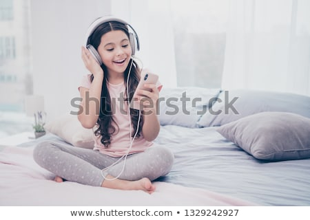 Pre teen girl is relaxing in the bed and listening to music with earphones Stock photo © Lopolo