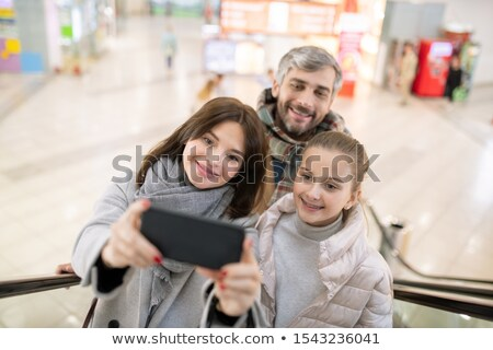 Happy mother, daughter and father making selfie on escalator in the mall Stock photo © pressmaster