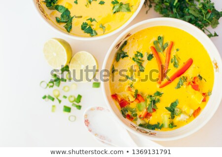 Bowl of fresh curry soup with red bell pepper, parsley against white background. Fresh vegetable dis Stock photo © vkstudio