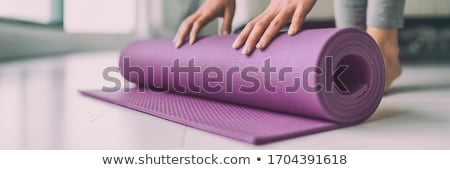 Yoga at home woman rolling pink exercise mat in living room starting warm up meditation zen well bei Stock photo © Maridav