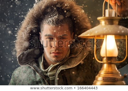 Brutal man walking under snowstorm at night lighting his way wit Stock photo © HASLOO