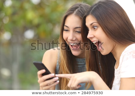 Shocked happy group of friends using mobile phones looking aside. Stock photo © deandrobot