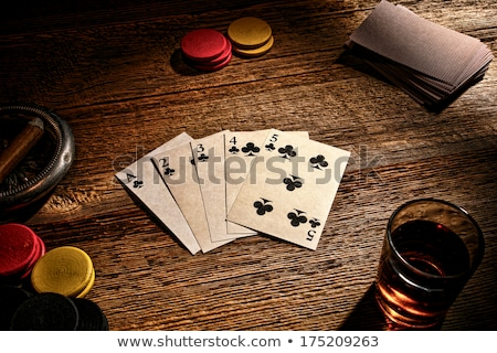 glass of whisky and playing cards on table stock photo © dolgachov