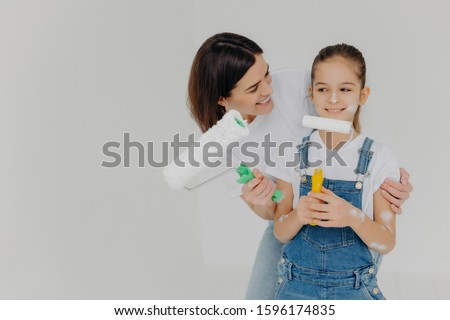 Caring mother embraces small daughter with love, paint walls of new house together, hold paint rolle Stock photo © vkstudio