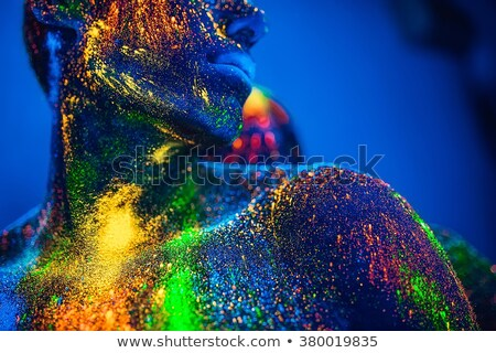 Woman close up on the background of fluorescent bulbs touches her face with her hands Stock photo © ElenaBatkova
