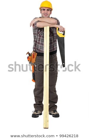 Stock photo: carpenter with arms resting on lumber holding handsaw