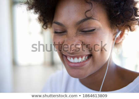 A close up shot of a woman with her eyes closed listening to her headphones while at the end of the  Stock photo © wavebreak_media
