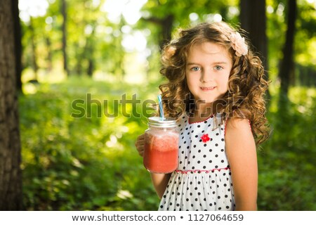 The little girl on straw with a basket of fruit against the wall of boards. Vertical format. Stock photo © Paha_L