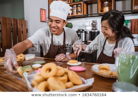 Smiling chefs couple dressed in aprons Stock photo © deandrobot