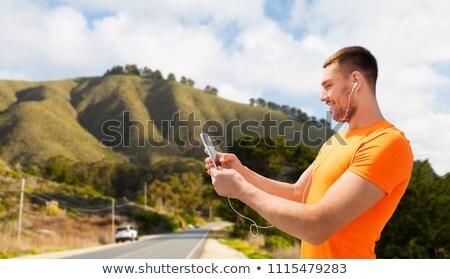 男 スマートフォン イヤホン 丘 フィットネス スポーツ ストックフォト © dolgachov