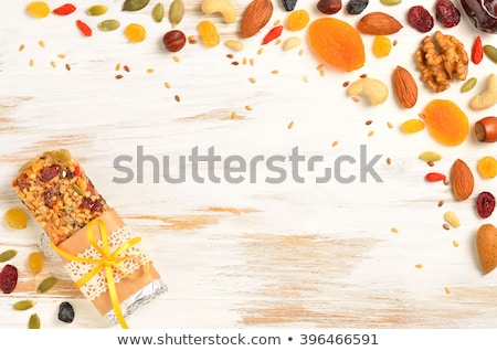 Homemade organic granola cereal bar with nuts and dried fruit on white background with oats and raw  Stock photo © DenisMArt
