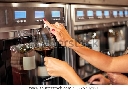 close up of woman with glass at wine dispenser Stock photo © dolgachov