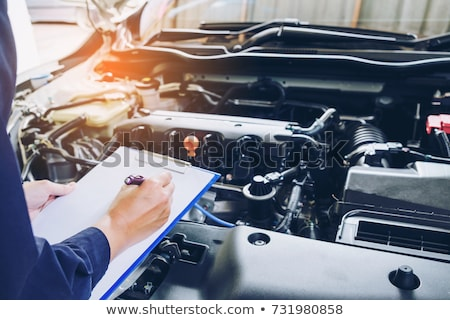 auto mechanic with clipboard at car workshop Stock photo © dolgachov
