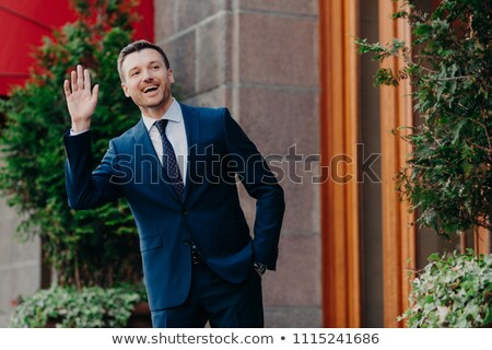 Shot of cheerful male banker in luxury black suit, waves with hand as notices friend on street, stan Stock photo © vkstudio