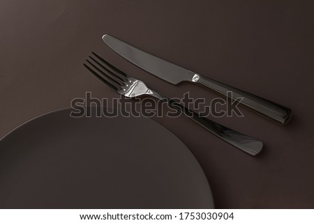 Empty plate and cutlery as mockup set on dark brown background, top tableware for chef table decor a Stock photo © Anneleven