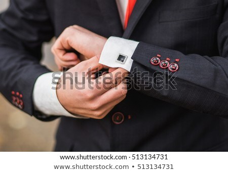 groom in a white shirt and red tie buttoning stock photo © ruslanshramko