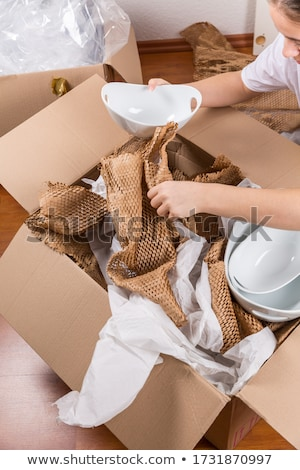 Detail of woman packaging fragile items using crumpled packing paper Stock photo © brebca