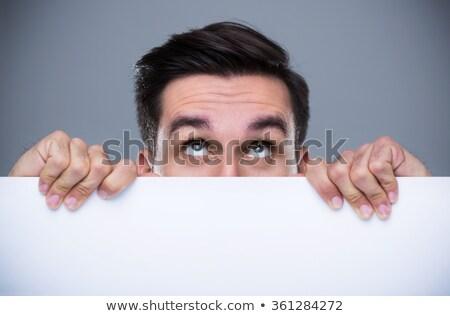 Bel homme cacher derrière studio sourire Photo stock © wavebreak_media