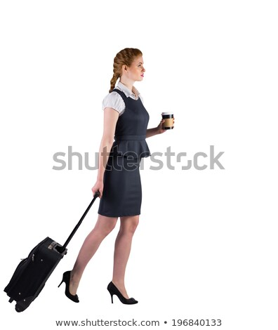 Stock photo: Redhead businesswoman pulling her suitcase holding coffee