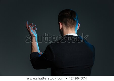 Back view of young man magician standing with raised hand Stock photo © deandrobot