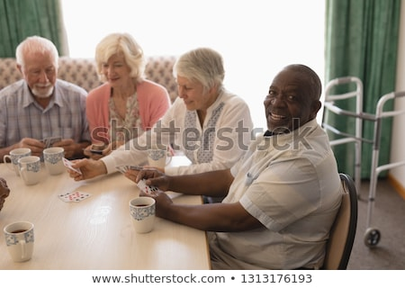 Front view of group of active senior people interacting with each other over a photo album  while se Stock photo © wavebreak_media