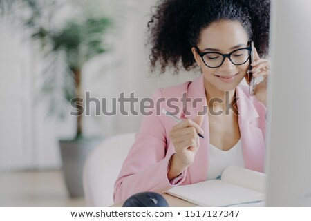 Smiling charming woman with curly hair, writes down information in notebook, gets consultancy via ce Stock photo © vkstudio