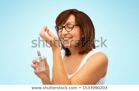 senior woman smelling perfume from her wrist Stock photo © dolgachov