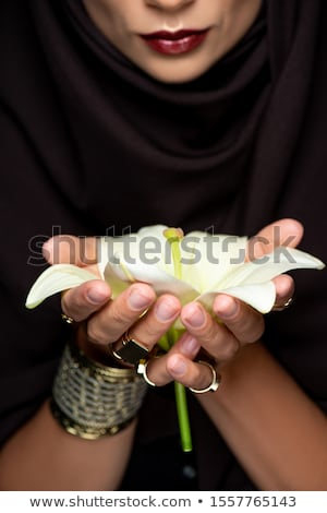 attractive young woman holding a lily flower stock photo © hasloo