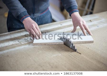 carpenter cutting wooden board with circular saw stock photo © kzenon