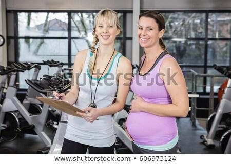 Uśmiechnięty trener schowek kobieta w ciąży siłowni Zdjęcia stock © wavebreak_media
