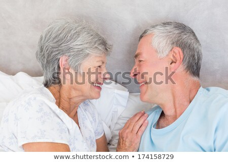 Senior couple lying heads to each other Stock photo © IS2