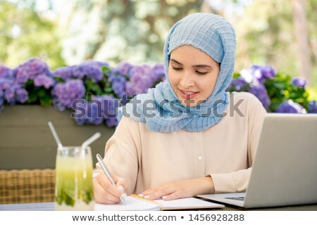 Pretty muslim student in hijab making notes in notebook outdoors Stock photo © pressmaster
