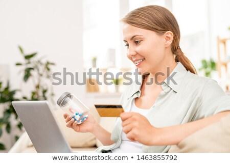 Happy girl looking through online drugstore for medicine Stock photo © pressmaster