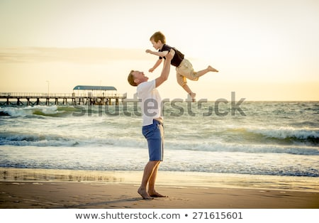 young happy father holding up in his arms little son putting him up at the beach in barefoot standin Stock photo © galitskaya