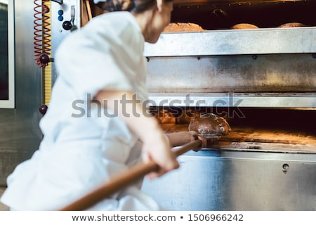 Baker putting bread in the bakery oven Stock photo © Kzenon