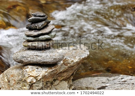 Stone pyramid cairn near river, buddhism Stock photo © dariazu
