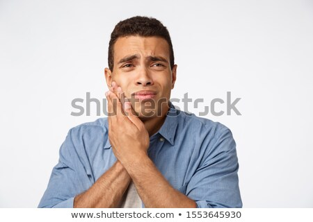 Medicine, people and emotions concept. Upset gloomy young man have discomfort, touch cheek and frown Stock photo © benzoix