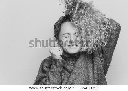 Lucky young cheerful female feels excited, keeps eyes shut and clenches fists, has curly light pony  Stock photo © vkstudio