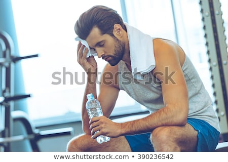 Image of young tired man in sportswear resting while working out Stock photo © deandrobot